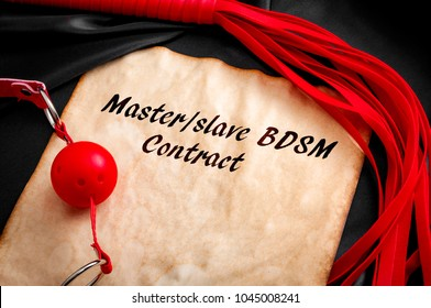 "Slave contract concept with a aged paper surrounded by a red flogger and a ball gag with the text ""Master/Slave BDSM contract"""