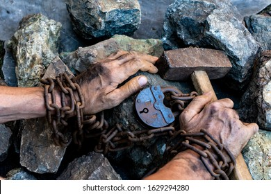 Slave hard work. Penal servitude. Slave chain tied hands hold a hammer. The desire to free oneself. The desire to break the shackles.