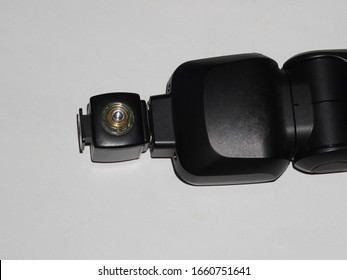 Slave unit attached to the mounting foot of a speedlight.