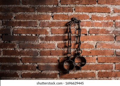 Slavery and bondage strong steel old shackles isolated on bricks background