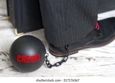 In slavery of credit concept with metal ball on chain and leg