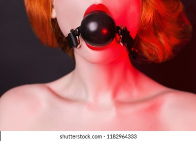 Slavery in society. Redhead hostage girl with gag on black. Sexual bdsm toy. Woman slavery. Slave attire for playing bdsm games. Frightened slave. Black leather bondage with gag. Scared hostage