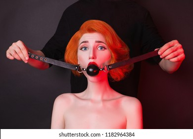 Slavery in society. Redhead victim girl with gag on black background. Sexual bdsm toy. Woman slavery. Attire for playing bdsm games. Black leather bondage with gag. Scared victim