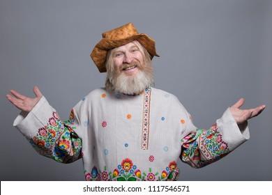 Slavic bearded man in a beautiful painted shirt and a birchbark hat