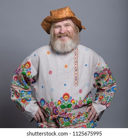 Slavic bearded man in a beautiful painted shirt and a birchbark hat