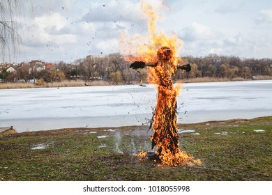 Slavic holiday of the end of winter. A large Shrovetide doll from straw burns on the river bank. Black smoke is visible