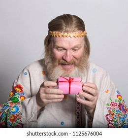 Slavic man in a beautiful national painted shirt with a gift in his hands