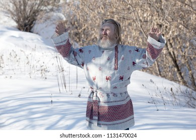 Slavic man in a beautiful national painted shirt on a spring day on the earth