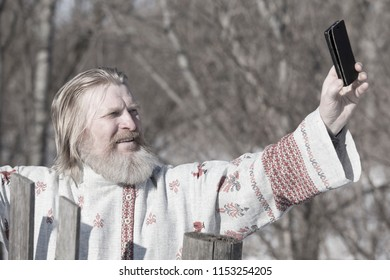 Slavic man in a beautiful national painted shirt on a spring day on the earth makes selfy