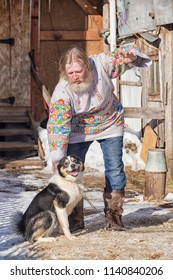 Slavic man in a beautiful painted shirt playing with a dog