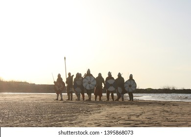 Slavic warriors reenactors with wearpons and shields posing outdoors at seaside standing in a row