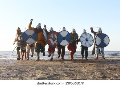 Slavic warriors reenactors with wearpons and shields training fighting outdoors at seaside , running at camera