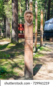 A Slavic wooden idol, a pagan god against the background of the siberian forest.