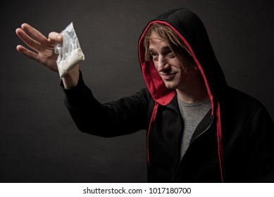 Sleazy guy in hood holding up little package with white powder and looking at it with suspicion. Isolated on background