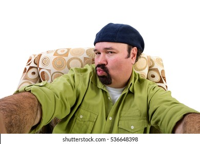 Sleazy overweight man in armchair blowing kiss and taking selfie, white background