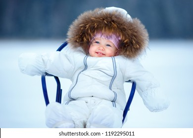 Sled and snow fun for kids. Baby sledding in snowy winter park. Little girl in warm white jacket and knitted hat sitting on sleigh. Family Christmas vacation
