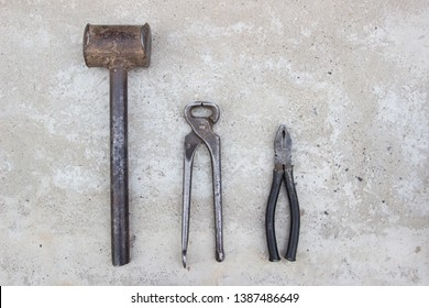 Sledge hammer, tongs, pliers, on concrete. Blacksmith tools, top view.