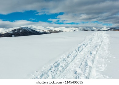 Sledge trace and footprints on winter mountain hill top and snow covered picturesque alp Chornohora ridge (Ukraine, Carpathian Mountains, tranquility peaceful view from Dzembronya village outskirts).