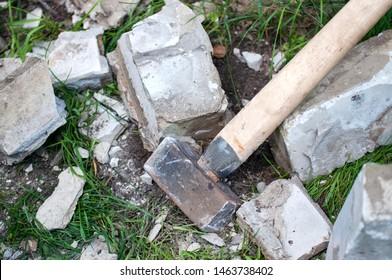sledgehammer on the grass with a broken brick