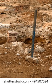 A sledgehammer standing in a pile of dirt and rubble at a sidewalk repair construction site.