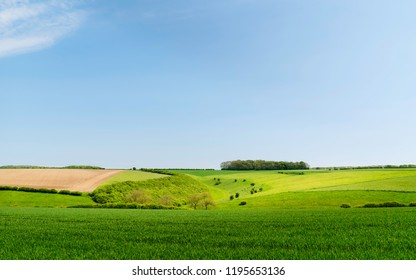 Sledmere, Yorkshire, UK. View across an agricultural landscape with wheat field on bright spring morning in the Wolds near Sledmere, Yorkshire, UK.