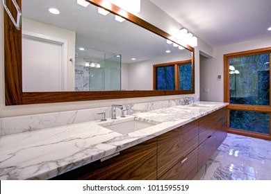 Sleek bathroom features double vanity cabinet with white gray marble countertop and rectangular undermount sinks atop marble floor