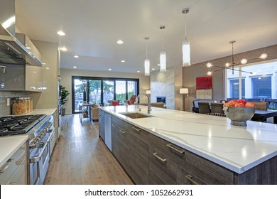 Sleek modern kitchen design with an island fitted with a gray and white quartz countertop.