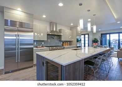 Sleek modern kitchen design with a long center island fitted with a gray and white quartz countertop, huge refrigerator and stainless steel hood.