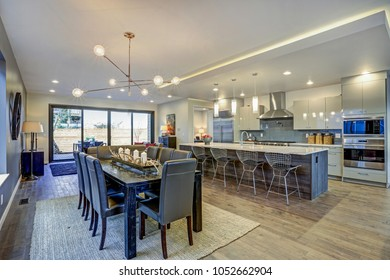 Sleek modern kitchen design with a long center island and spacious dining area with black wooden table, leather chairs atop sisal rug.
