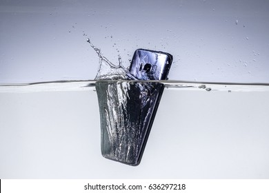 A sleek, modern smartphone makes a splash as it is dropped in the water to test its waterproof construction