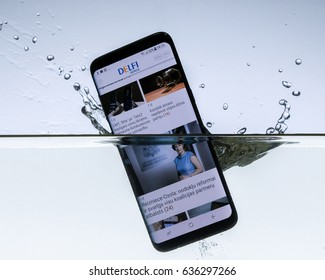 A sleek, modern smartphone with open web browser on its screen makes a splash as it is dropped in the water to test its waterproof construction