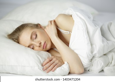Sleep. Beautiful young woman sleeping in bed in the morning. Portrait of an attractive girl resting in a comfortable bed with a pillow and white bedding. Bedroom. Close up.