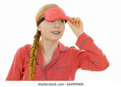 Sleep bedroom accessories concept. Happy sleepy woman wearing pink eye band and pajamas.