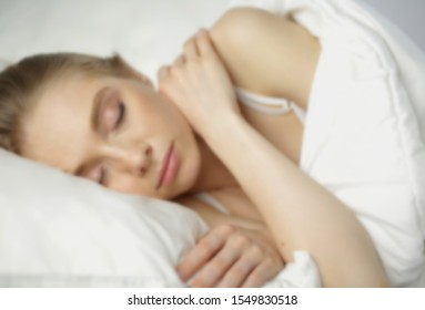 Sleep. Blur background. Beautiful young woman sleeping in bed. Morning dream. Attractive girl resting in a comfortable bed on a pillow. Bedroom. Close up. Copy space for your text.