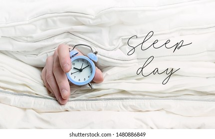 Sleep day. alarm clock in hand among blankets. Hand holding alarm clock among blankets, in bed. concept of laziness, world sleep day, time to get up.