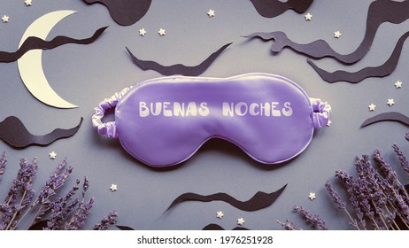 Sleep mask with dry lavender flowers. Text Buenas Noches means Good night in Spanish. Silver grey paper background with black clouds and Moon. Aromatherapy, scented herbs. Creative top view, flat lay.