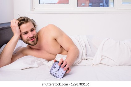 Sleep regime habit. Man unshaven lay bed hold alarm clock. Man unshaven bearded wakeful face having rest. Stick schedule same bedtime wake up time. Enough sleep for him. Regulate your bodys clock.