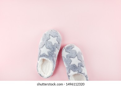 Sleep. Soft fluffy slippers on pink background. Creative conceptual top view flat lay in minimal style. Rest, good night, insomnia, relaxation, tired, hygge concept