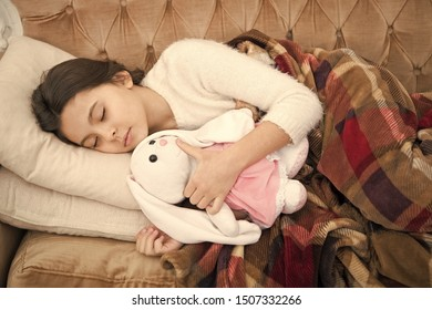 Sleep with toy. Girl enjoy evening time with favorite toy. Kid lay bed and hug bunny toy couch pillow blanket background top view. Girl child wear pajamas hug bunny. Play soft toy before go sleep.
