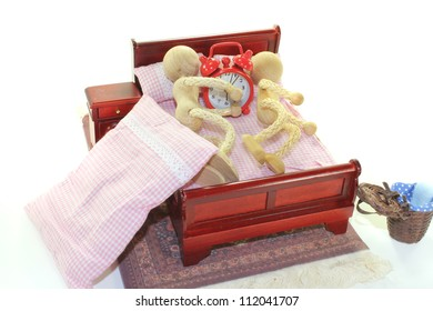 Sleep - two wooden doll and alarm clock in bed with bedside table and plaid bedding
