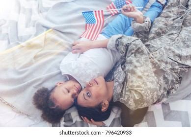 Sleep well. Cute tired young girl lying on the bed with her mother and sleeping while being hugged by her