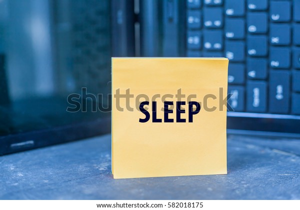 SLEEP word on paper note on wooden table over blurry laptop as a background