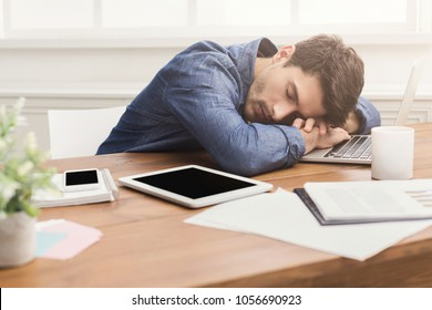 Sleep at work. Tired, overworked businessman napping at workplace in modern office interior, copy space
