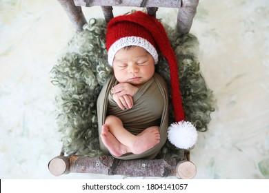 Sleeper newborn baby in a Christmas Santa cap, two week old.