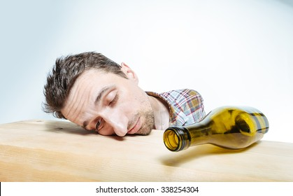 Sleeping alcoholic. Drunk man with empty wine bottle, sleeping on the table.