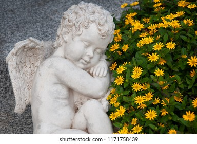 sleeping angel made of clay on a grave surrounded by yellow Mexican creeping zinnia
