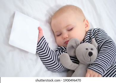 A sleeping baby with a favorite soft toy mouse and a white card in his hand. Place for text. Copy space. Child in striped pajamas. Close-up portrait, selective focus