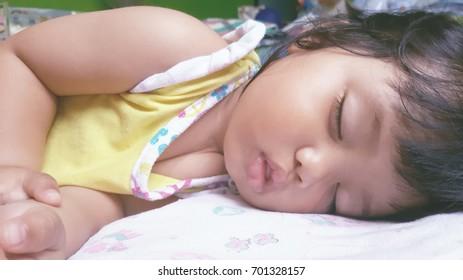 Sleeping baby girl in bed.