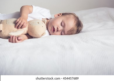 Sleeping baby in his crib, holding a teddy bear.