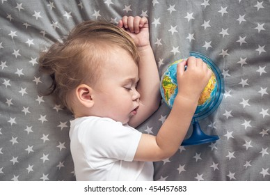 Sleeping baby holding a globe in his hands and dreaming about future travels.